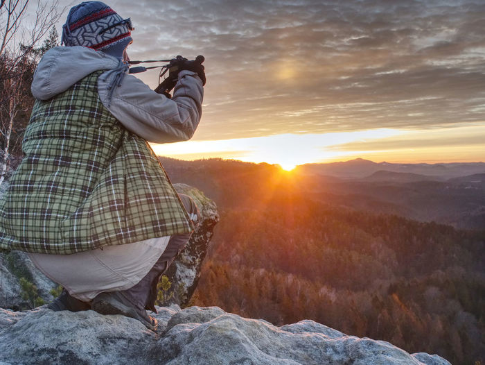 Hiker woman photographer takes impresive photos from sharp cliff edge.