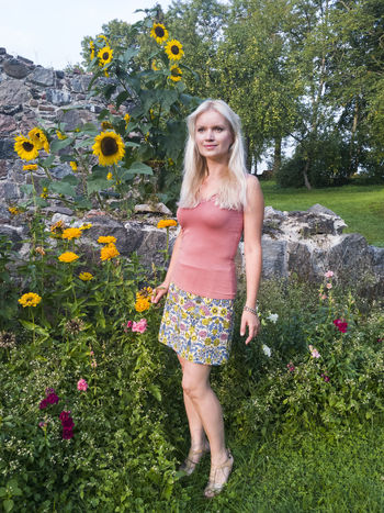 Blond woman standing by sunflowers in Estonia. Beautiful Woman Blond Hair Day Flower Full Length Lifestyles Nature One Person Outdoors People Plant Real People Standing Standing Sunflower Wall Young Adult Young Women