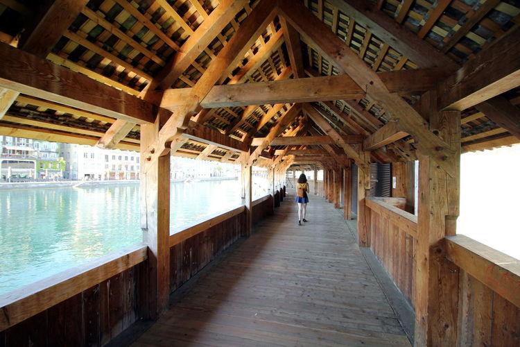 Rear view of teenage girl walking on covered bridge by lake