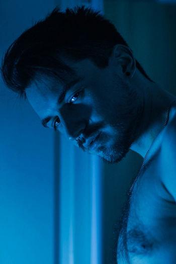 Portrait of shirtless man in darkroom