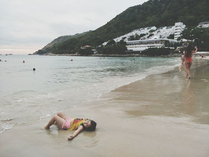 Girl Lying On Shore At Beach Against Mountain