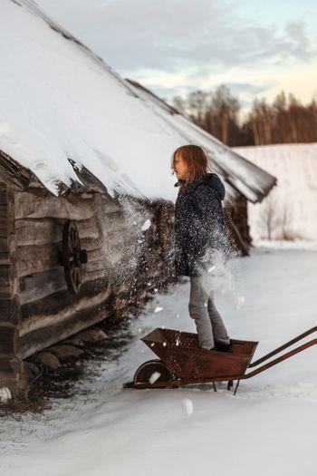 Full length of person on wheelbarrow against the winter snow