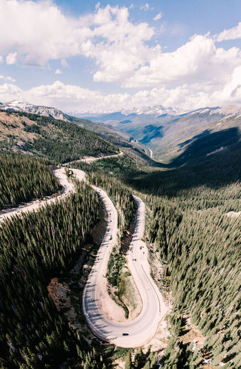 Aerial view of winding road on mountains against cloudy sky