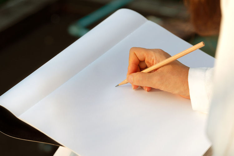 Hand sketching on drawing book outdoor. Woman hands sketching on drawing book with brown pencil early in the morning . Artist Hands Morning Light SKETCH DESIGN Woman Designer  Drawing - Activity Outdoors Pencil Drawing Sketchbook