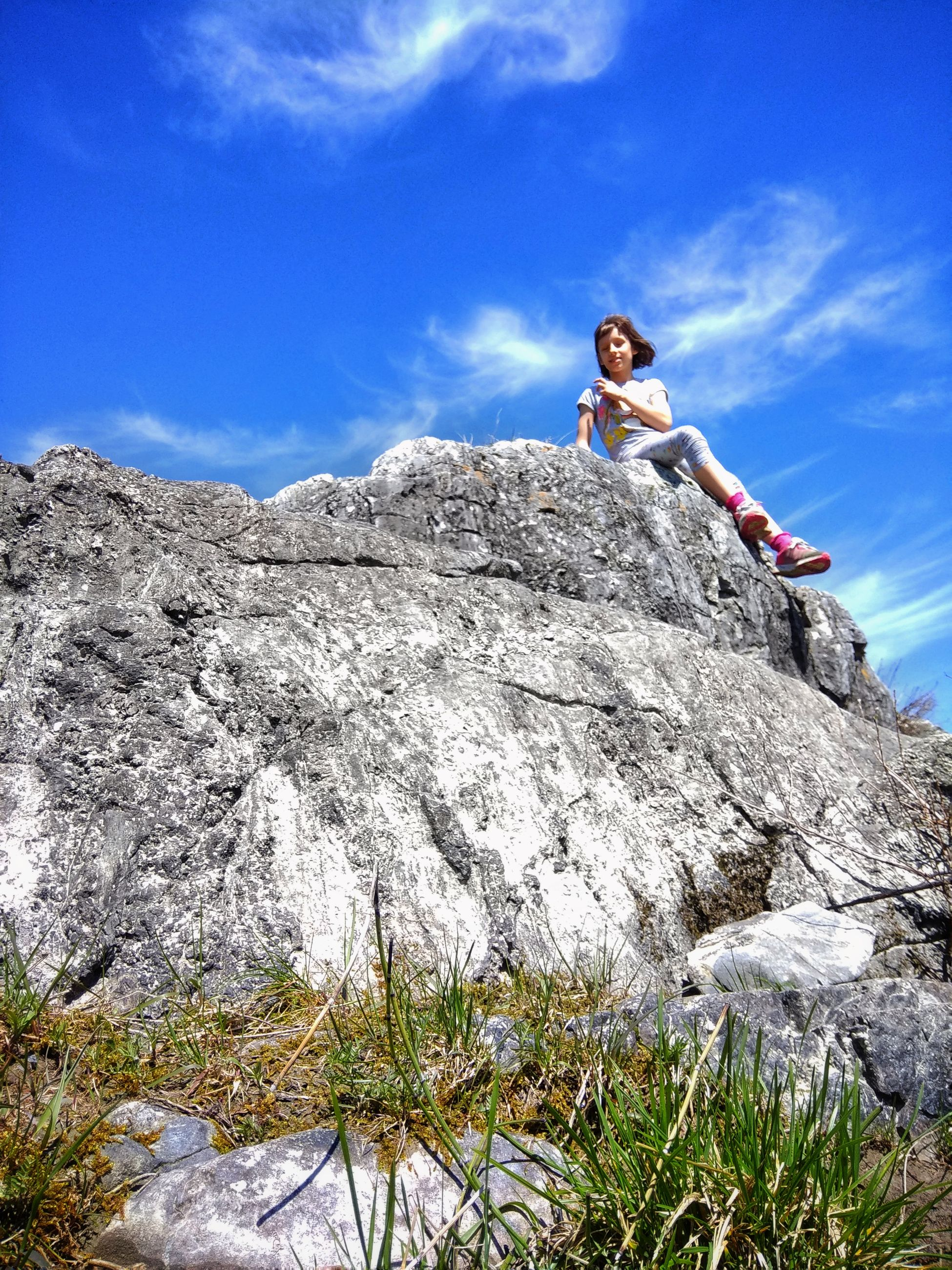 leisure activity, one person, low angle view, sky, rock, real people, solid, lifestyles, full length, casual clothing, rock - object, young adult, climbing, adventure, sport, nature, women, day, cloud - sky, outdoors