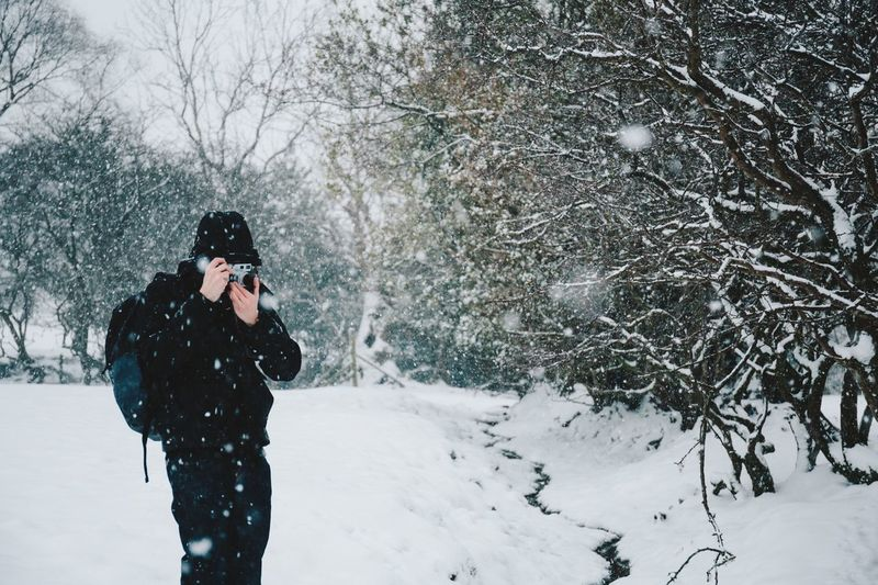 Man In Warm Clothing Photographing During Winter