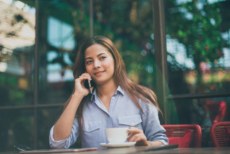 Young woman using phone while sitting on table at sidewalk cafe