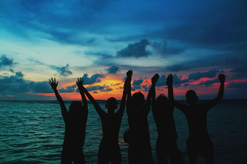 Silhouette people with arms raised standing in sea during sunset