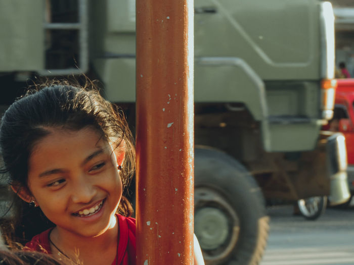 Close-up of smiling girl looking away by pole