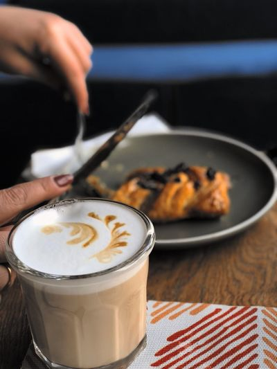 Good Morning EyeEm Selects Food And Drink Human Hand Coffee - Drink Coffee Cup Drink Refreshment Real People One Person Indoors  Human Body Part Table Food Freshness Frothy Drink Holding Close-up Focus On Foreground Plate Cafe Sweet Food