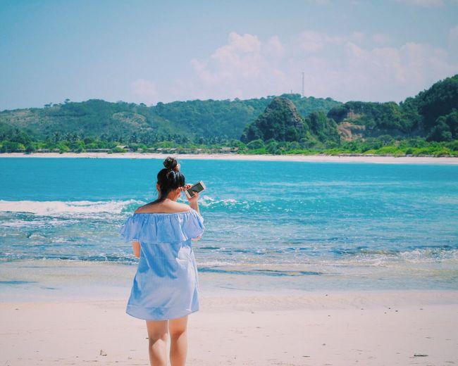 Woman Standing On Calm Beach