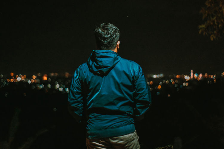 Rear view of man looking at illuminated city at night