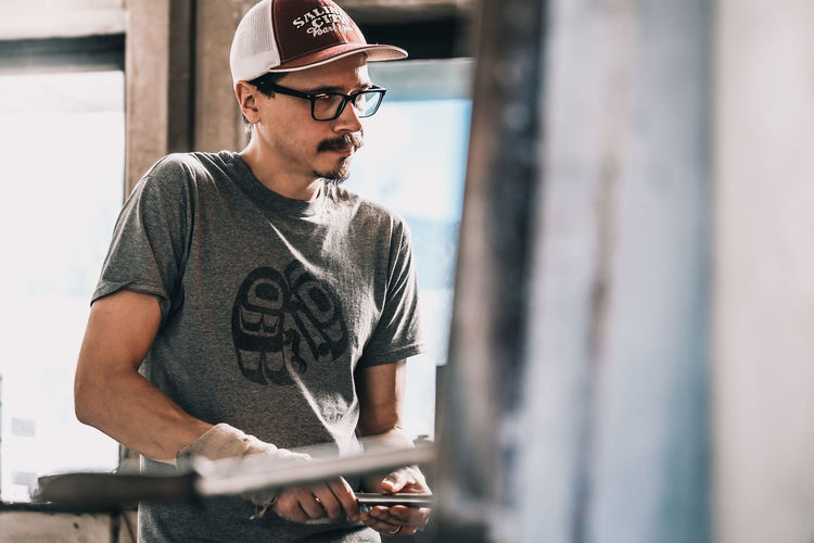 Working Working Man Workshop Baseball Cap Cap Casual Clothing Communication Day Eyeglasses  Focus On Background Indoors  Lifestyles One Person People Real People Standing Young Adult Young Men Business Stories