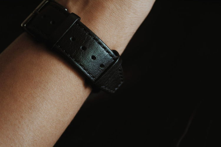 Cropped hand wearing wristwatch against black background