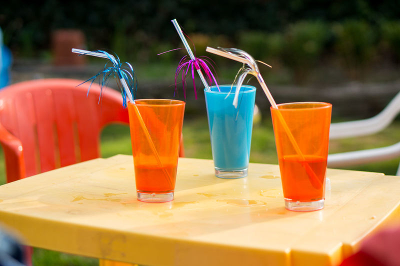Colorful glasses with decorative straws on table at restaurant