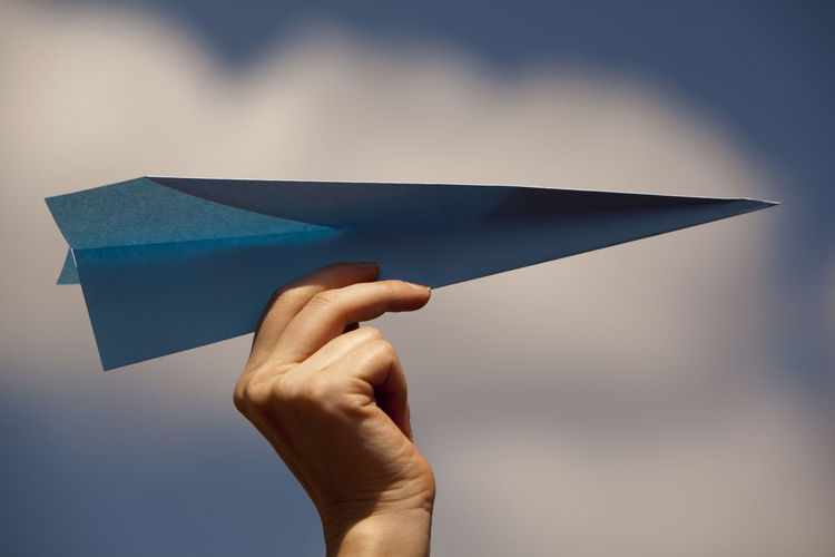 Cropped hand of woman holding paper airplane against sky