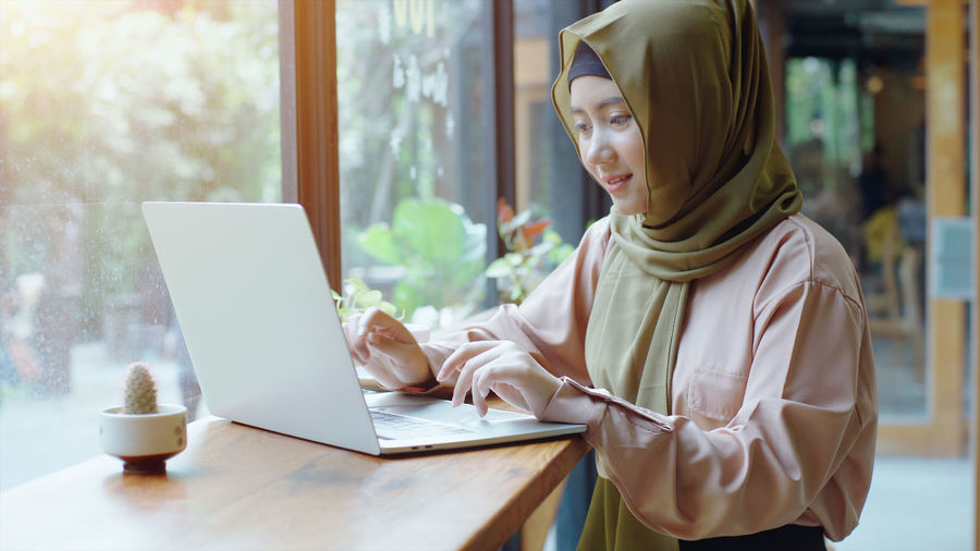 Young woman using laptop on table