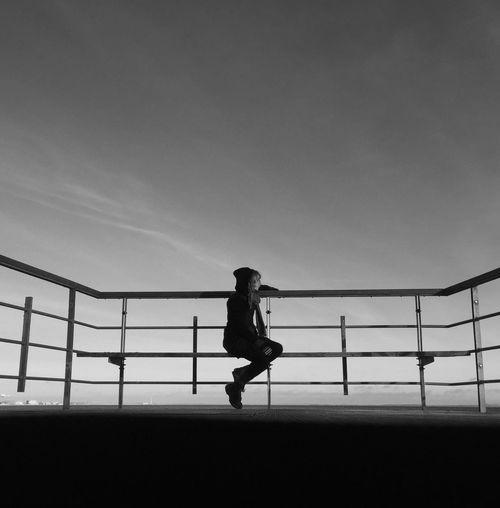 Girl sitting by railing at promenade against sky
