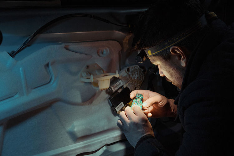Close-Up Of Man Repairing Vehicle At Night