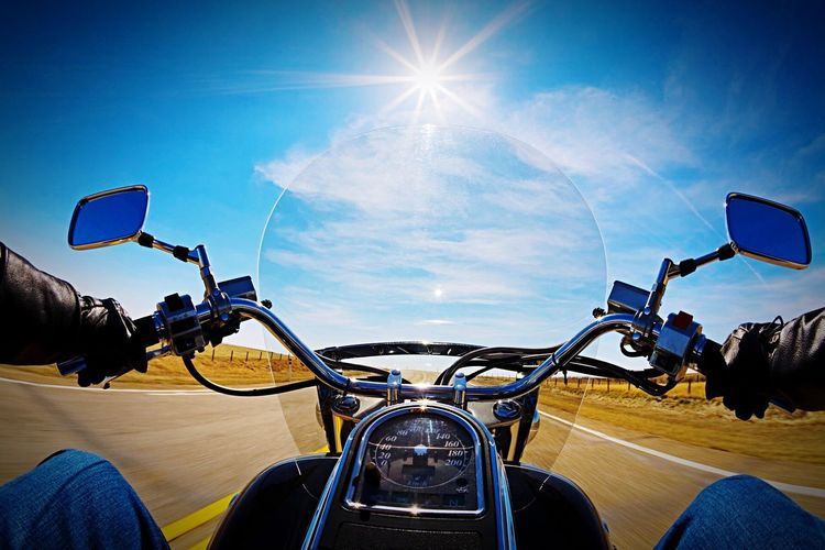 Motorbike Speeding In Front Of Long Rural Road Against Sun