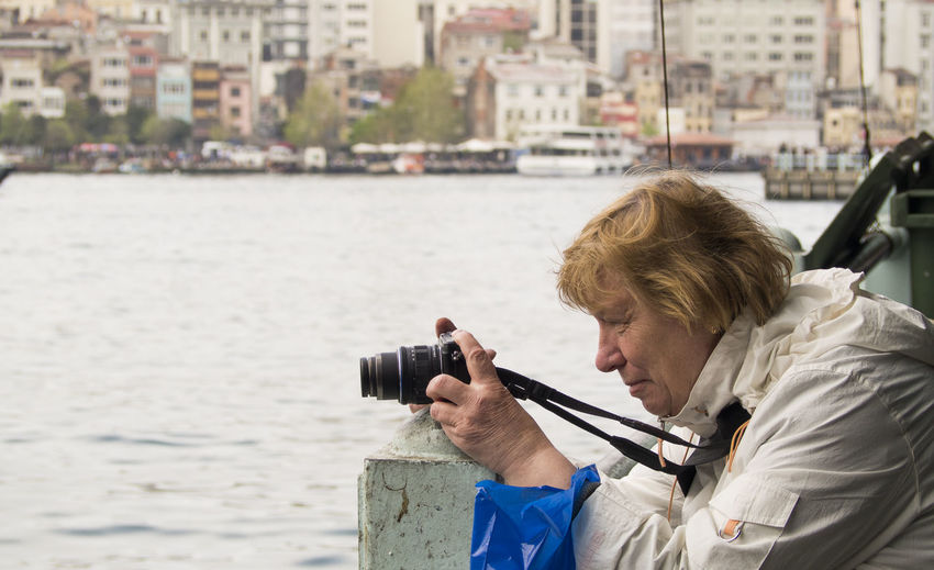 Side view of mature woman photographing straits