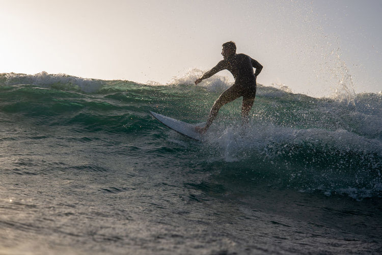 Water Leisure Activity Splashing Lifestyles Motion Sea Real People Sport One Person Men Aquatic Sport Wave Waterfront Sky Surfing Adventure Nature Extreme Sports Enjoyment Skill  Outdoors Power In Nature