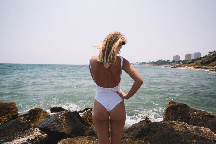 Rear View Of Seductive Woman Wearing One Piece Swimsuit While Standing At Beach