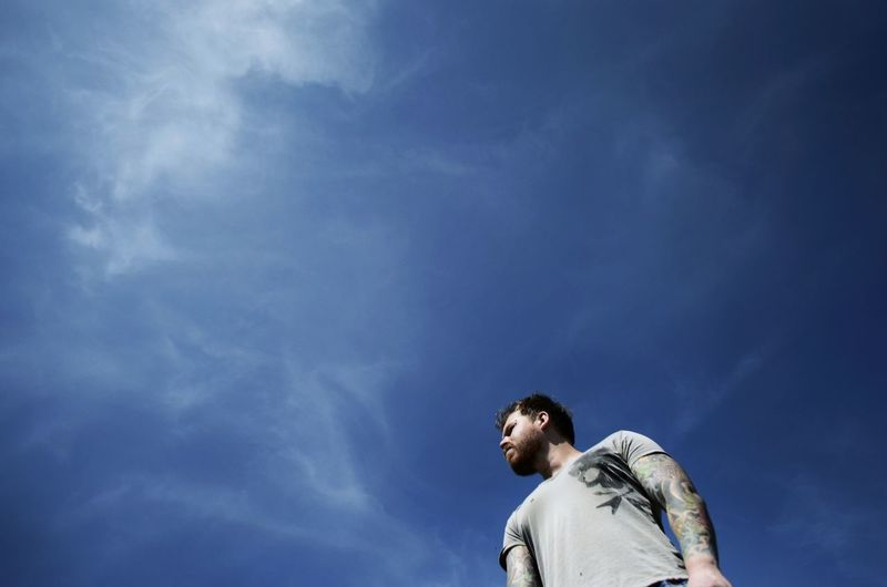 Low angle view of man standing against sky