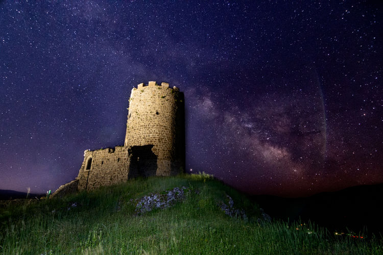 Castle on field against sky at night