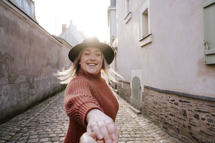 Portrait of woman holding hand in alley