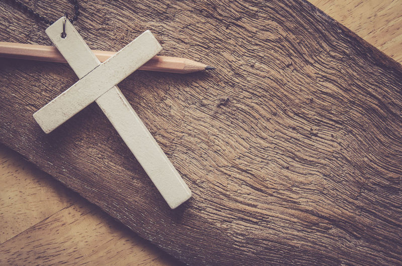 High Angle View Of Cross And Pencil On Wood