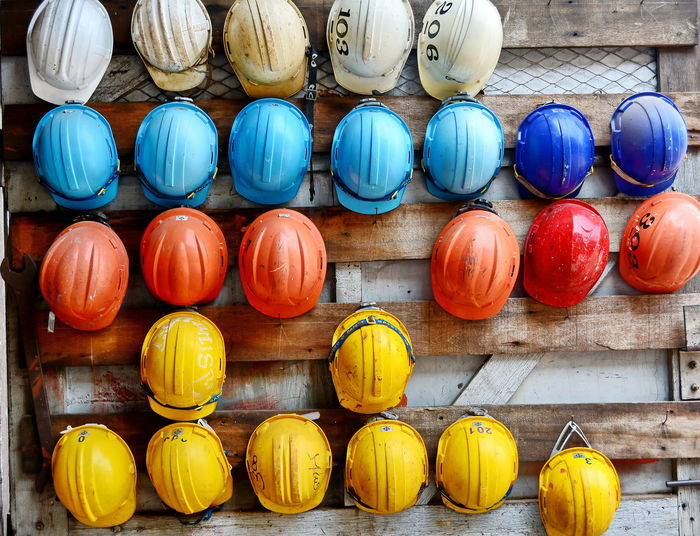 colorful safety helmets Helmet Safety Engineering Work Worker Site Structure Architecture Colorful Red Blue Yellow White Orange Arrangement In A Row Repetition Barrel Storage