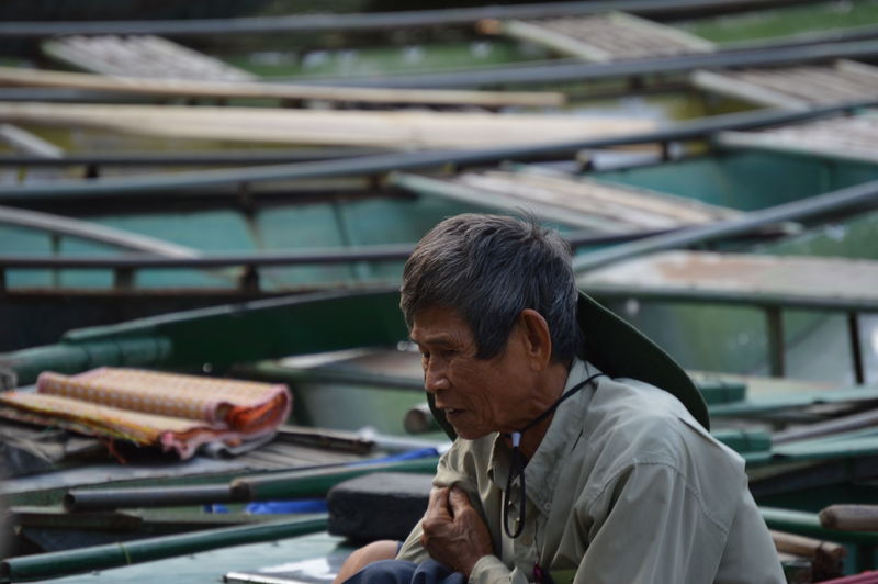 Senior man sitting against nautical vessels