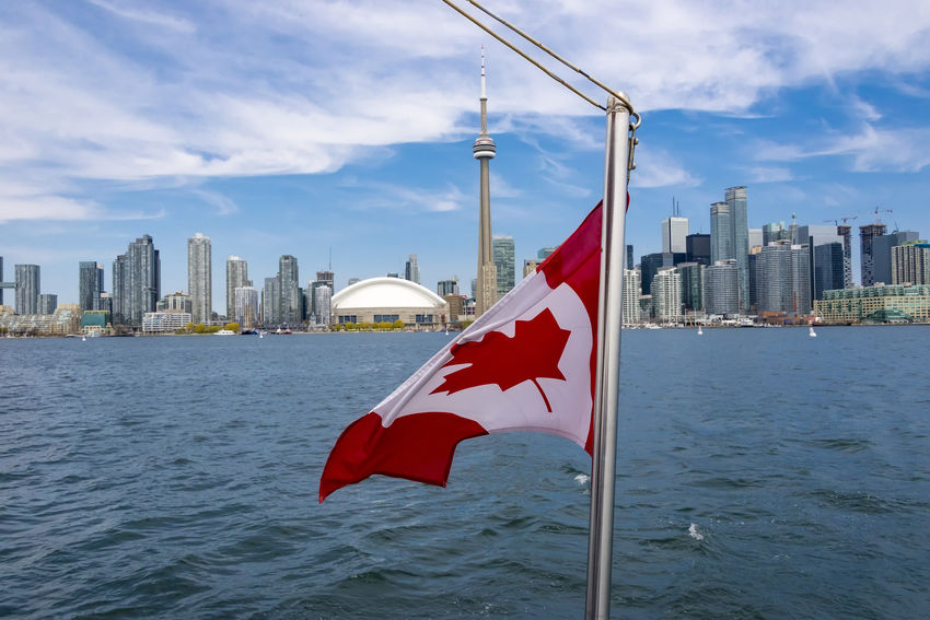 Canadian Flag waving in tourist boat with Toronto Canada skyline in the background. Selective focus on the flag. Architecture Built Structure Canadian Flag City Cloud - Sky CN Tower Cruise Culture Flag Flying Lake Ontario National Flag No People Outdoors Patriotism Rogers Centre Sky Toronto Toronto Canada Toronto Cityscape Toronto Skyline Tourist Boat Trip Travel Destinations Water Waving