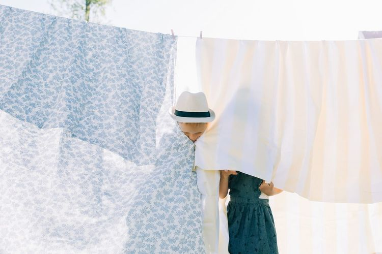 Clothes drying on clothesline against white wall