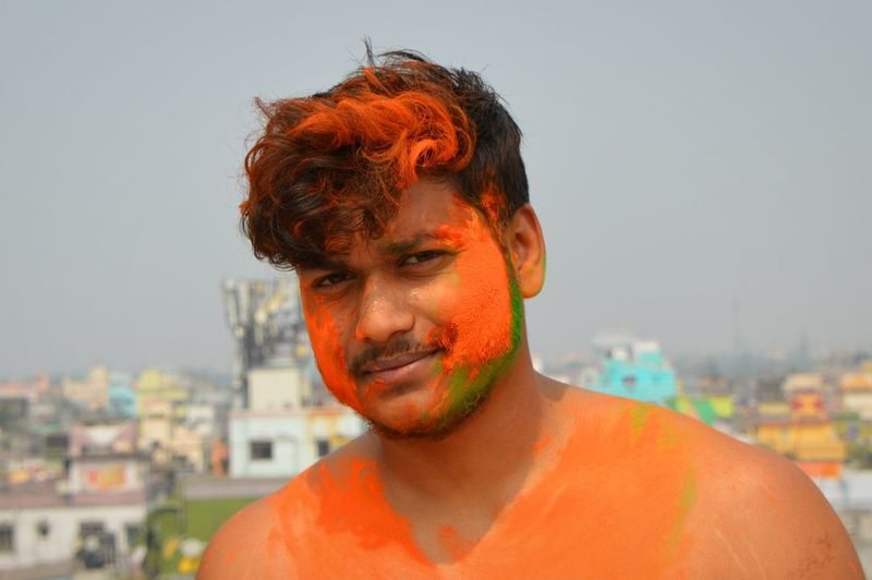Portrait of shirtless man with orange powder paint on face against sky