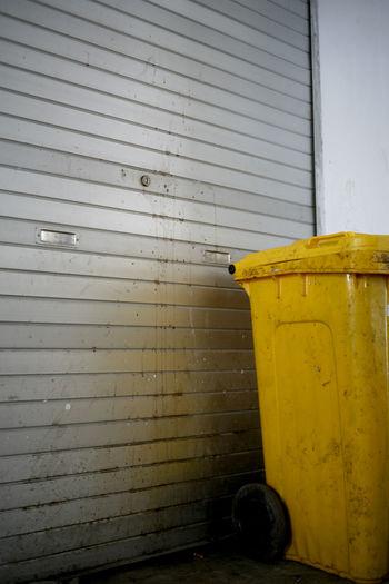 Garbage bin against wall