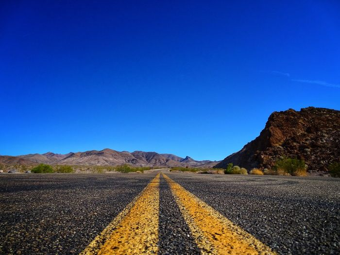 Surface level of road against blue sky