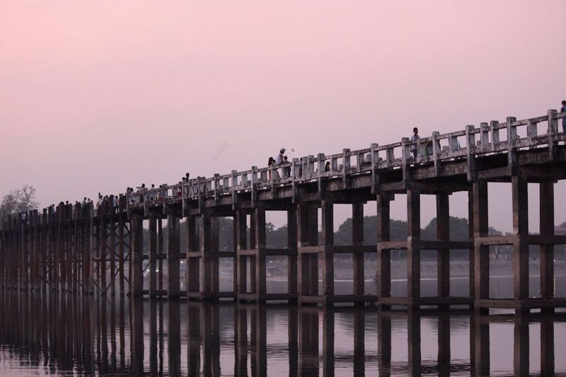 U bein bridge over lake against clear sky during sunset