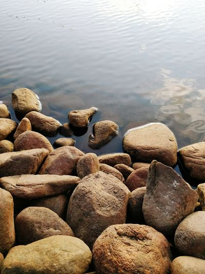 Close-up of pebbles in sea