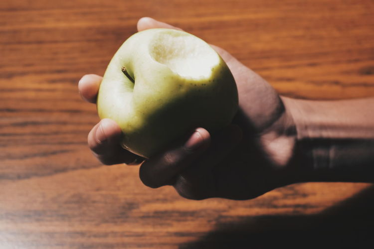 Cropped Hand Holding Apple At Wooden Table