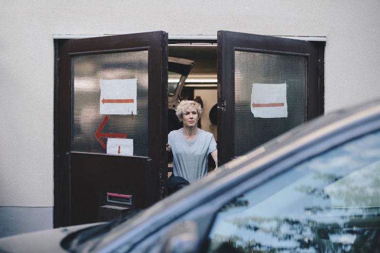 Portrait of woman standing by window