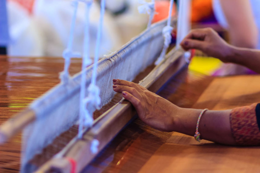 Weaver using small loom or weaving machine for weaving fabric. Weaver is weaving show and teaching to the tourist at the night market. Weave Weaves Close-up Day Human Hand Indoors  Loom One Person Real People Selective Focus Table Weave Pattern Weaved Weaver Weaving Weaving Loom Weaving Machine Women Wood - Material Working