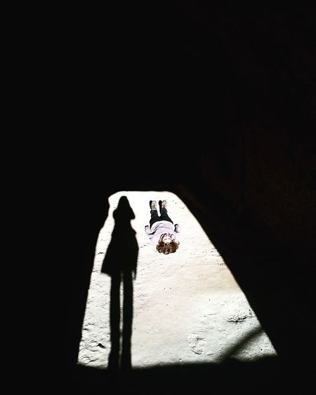 High angle view of girl lying on field in cave