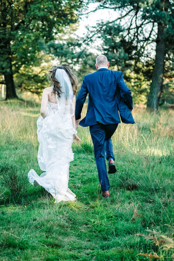 Rear view of couple walking on lawn