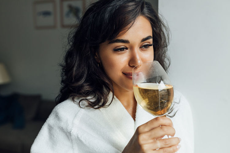 Close-up of smiling woman drinking wine while standing at home