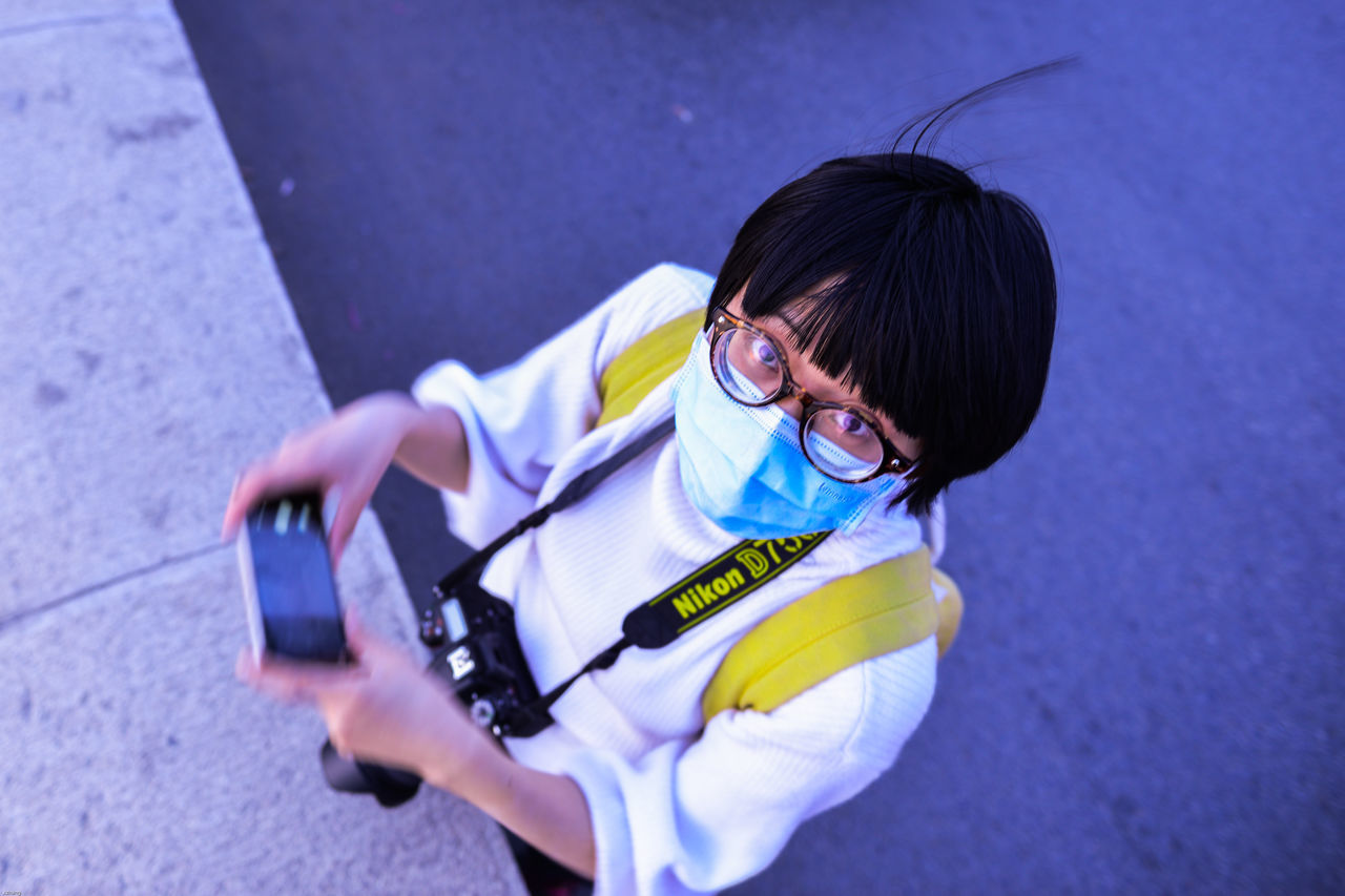 real people, one person, childhood, communication, holding, high angle view, outdoors, leisure activity, casual clothing, lifestyles, wireless technology, elementary age, girls, day, full length, technology, eyeglasses