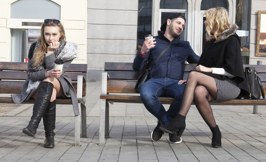 Friends sitting on bench in city
