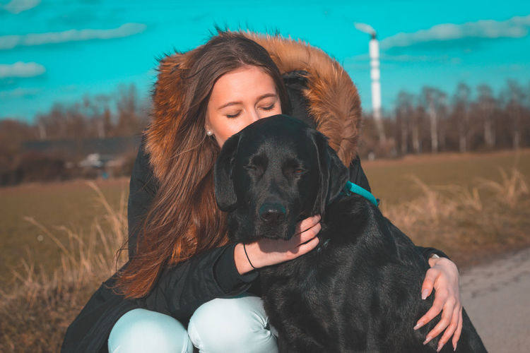Portrait Of Woman With Dog On Roadside During Winter