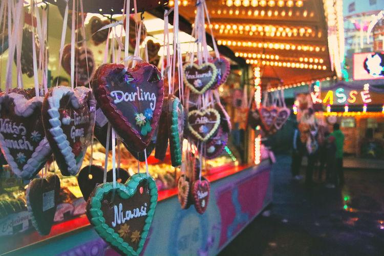 People in illuminated carousel at amusement park